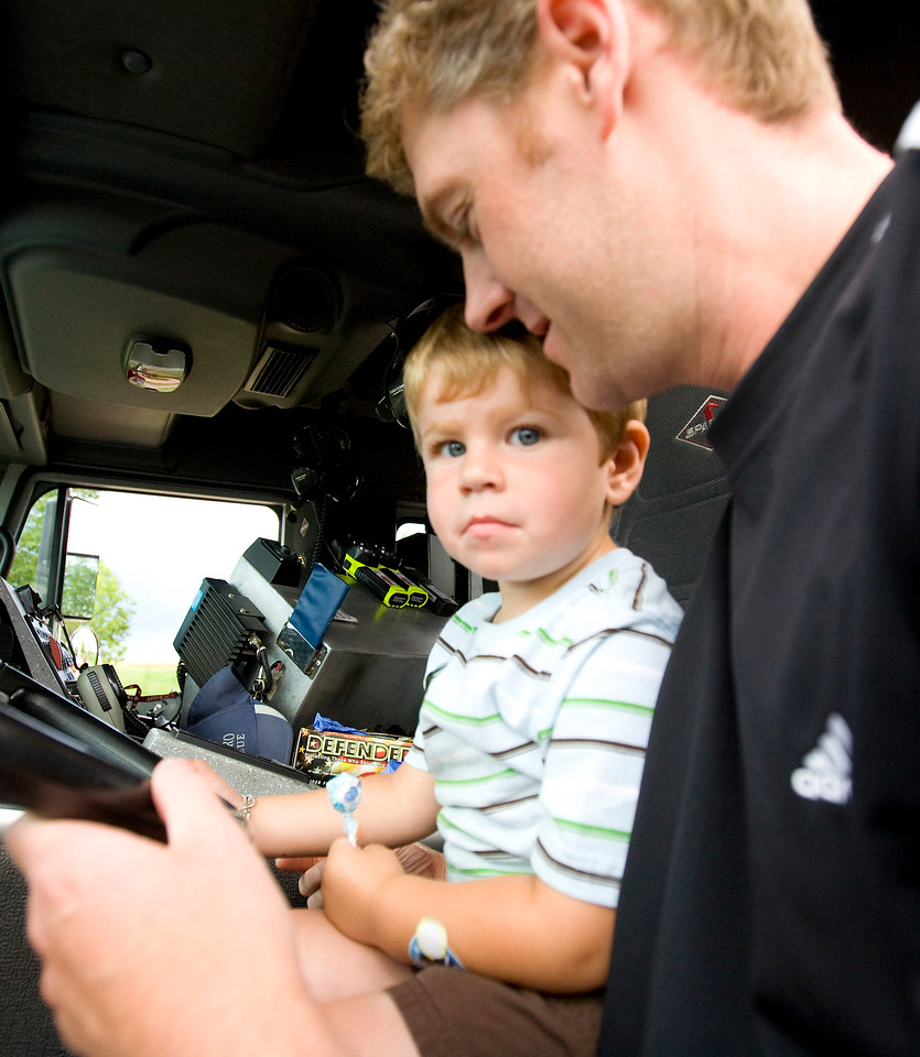 Drew Socia, age 2, pretends to drive the North Metro Fire truck with help from his dad Brian during the National Night Out at the Broomfield County Commons on Aug. 3, 2010. Photo by Matt Kelley/for the Enterprise