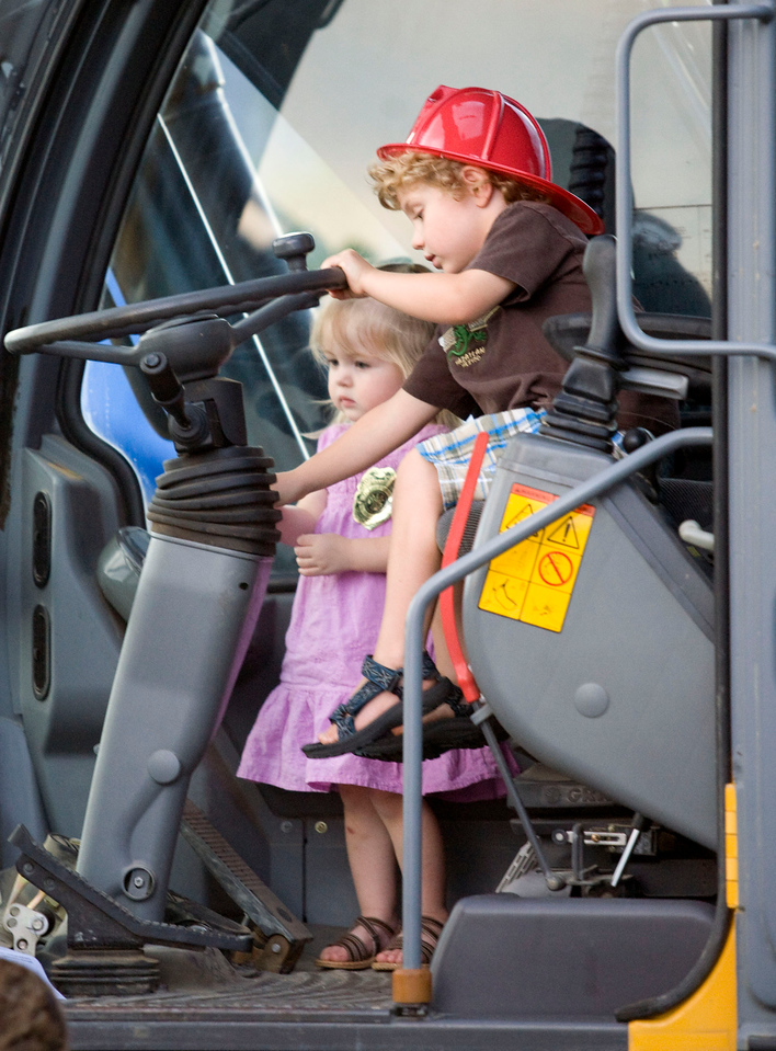 Lincoln Hastings, age 3, drives a tractor while his sister Aniston, 2, looks on during the National Night Out at the Broomfield County Commons on Aug. 3, 2010. Photo by Matt Kelley/for the Enterprise