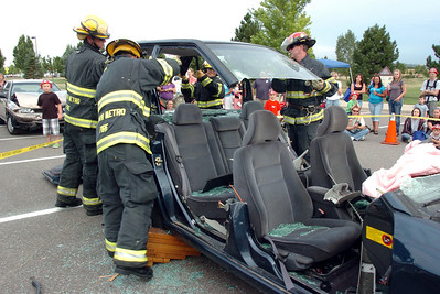 North Metro Fire firefighters remove the top of a car during an extrication demonstration for National Night Out at the Broomfield County Commons on Tuesday.  August 2, 2011 staff photo/ David R. Jennings