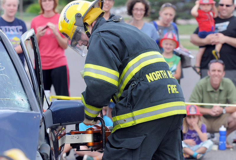 North Metro Fire firefighter Nick Ammon opens the door of a car during the car extrication demonstration at National Night Out at the Broomfield County Commons on Tuesday.<br /> <br /> August 2, 2011<br /> staff photo/ David R. Jennings