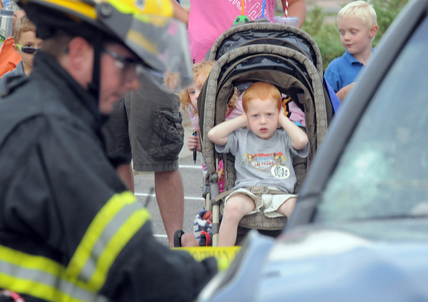 Kade Kohler, 3, covers his ears while watching North Metro Fire firefighters demonstrate a car extrication during National Night Out at the Broomfield County Commons on Tuesday.<br /> <br /> August 2, 2011<br /> staff photo/ David R. Jennings