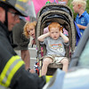 Kade Kohler, 3, covers his ears while his sister Kenadee, 3, peaks around the stroller to watch North Metro Fire firefighters demonstrate a car extrication during National Night Out at the Broomfield County Commons on Tuesday.<br /> <br /> <br /> August 2, 2011<br /> staff photo/ David R. Jennings