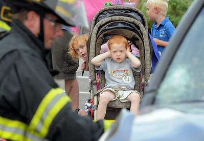 Kade Kohler, 3, covers his ears while his sister Kenadee, 3, peaks around the stroller to watch North Metro Fire firefighters demonstrate a car extrication during National Night Out at the Broomfield County Commons on Tuesday.   August 2, 2011 staff photo/ David R. Jennings