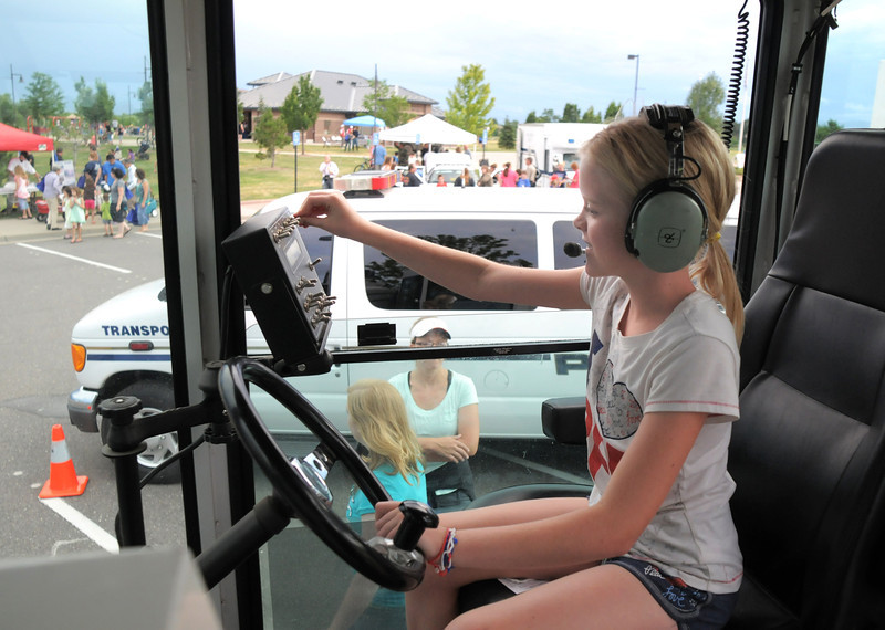 Kelly Myers, 10, plays with switches and chats to the front cab on the road stripe painting  truck during National Night Out at the Broomfield County Commons on Tuesday.<br /> <br /> August 2, 2011<br /> staff photo/ David R. Jennings