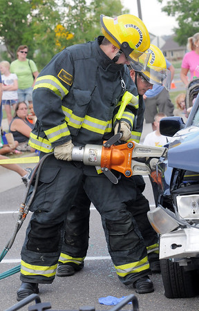 North Metro Fire firefighters Nick Ammon, left, and Shane Dougherty demonstrate a car extrication during National Night Out at the Broomfield County Commons on Tuesday.<br /> <br /> August 2, 2011<br /> staff photo/ David R. Jennings