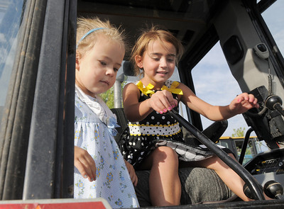 Payton Delier, 6, right, and her sister Taylor, 3, play with the controls of a backhoe during National Night Out at the Broomfield County Commons on Tuesday.  August 2, 2011 staff photo/ David R. Jennings