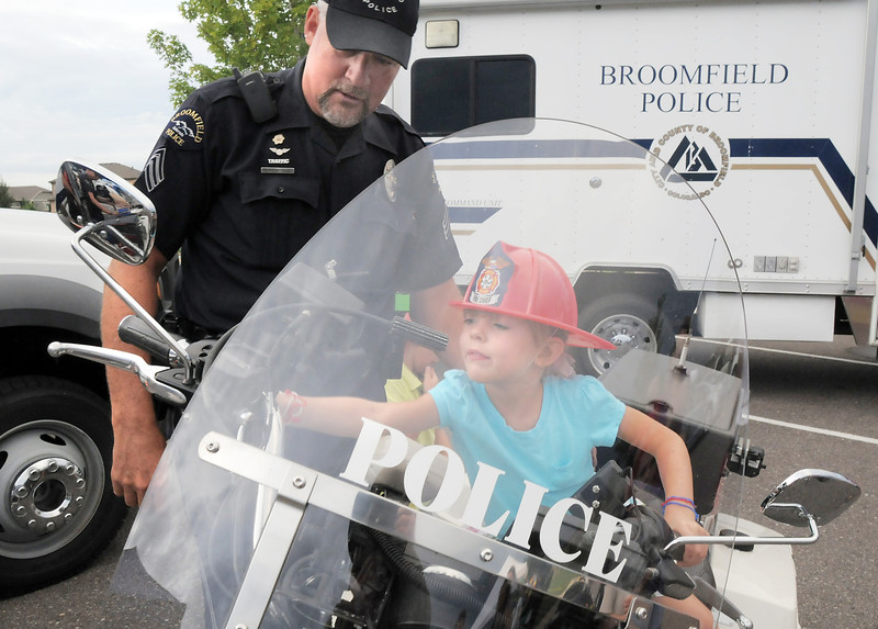 Broomfield Police Sgt. Rick Kempsell watches Kathleen Brening, 5, flip switches while sitting on his motorcycle during National Night Out at the Broomfield County Commons on Tuesday.<br /> <br /> <br /> August 2, 2011<br /> staff photo/ David R. Jennings