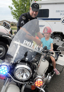 Broomfield Police Sgt. Rick Kempsell watches Kathleen Brening, 5, sit on his motorcycle during National Night Out at the Broomfield County Commons on Tuesday.   August 2, 2011 staff photo/ David R. Jennings