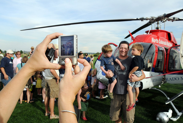 Lauren Ng, left, takes a picture of her family Quin holding their sons Caleb, 2, and Eli, 3, in front of North Colorado Medical Center helicopter during National Night Out at County Commons Park on Tuesday.<br /> <br /> <br /> August 4, 2009<br /> staff photo/David R. Jennings