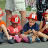 Wearing their fire hats, Conner Boehnke, 6, left, Medina Allen, 2, Micah Allen, 3, and Emily Allen, 6, wait for the North Metro Fire Rescue extrication demonstration during National Night Out at County Commons Park on Tuesday.<br /> <br /> <br /> August 4, 2009<br /> staff photo/David R. Jennings