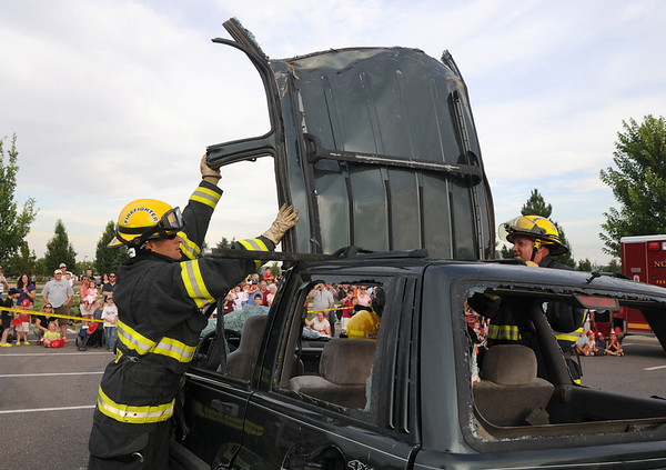 North Metro Fire Rescue District firefighters Eric Young, left, and Wayne Becohlavy move the roof off of a vehicle during an extrication demonstration at National Night Out at County Commons Park on Tuesday.<br /> <br /> <br /> August 4, 2009<br /> staff photo/David R. Jennings