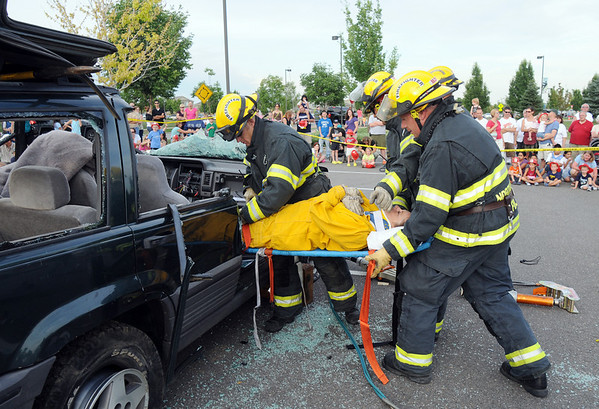 North Metro Fire Rescue District firefighters carry volunteer Pam Kutchen out of a car for an extrication demonstration during National Night Out at County Commons Park on Tuesday.<br /> <br /> <br /> August 4, 2009<br /> staff photo/David R. Jennings