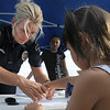 Broomfield Police officer Meredith Durham takes the finger prints of  Catalina Hiller, 4 1/2. during National Night Out at County Commons Park on Tuesday.<br /> <br /> <br /> August 4, 2009<br /> staff photo/David R. Jennings