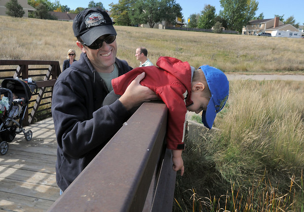 DAve Fife and his son Evander, 2, look for wildlife from the bridge during the Broomfield Nature Program at Josh's Pond on Wednesday.<br /> October 5, 2011<br /> staff photo/ David R. Jennings