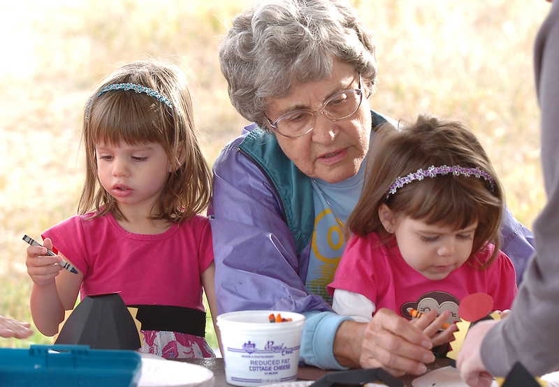 Marian Seber, center helps her 2 1/2 year old granddaughers Lauren, left, and Isabelle Rudland make coyote masks during the Broomfield Nature Program at Josh's Pond on Wednesday.<br /> October 5, 2011<br /> staff photo/ David R. Jennings
