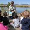 Volunteer Karen Steele reads a book about coyotes during the Broomfield Nature Program at Josh's Pond on Wednesday.<br /> October 5, 2011<br /> staff photo/ David R. Jennings