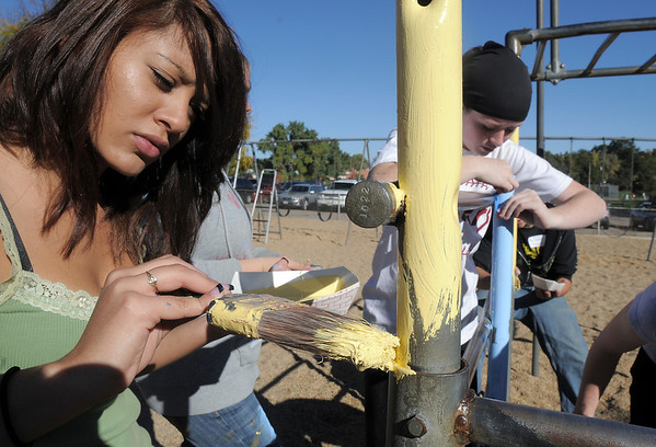 New Vista High students Regina Mata, 16, left, helps paint playground equipment while Michaela Johnson, 14, tapes off sections at Emerald Elementary School on Wednesday. <br /> October 16, 2011<br /> staff photo/ David R. Jennings