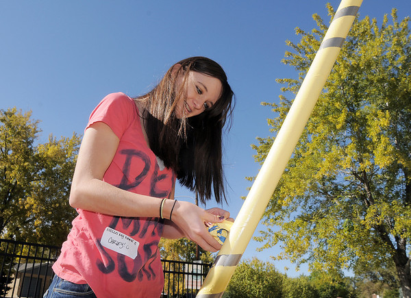 New Vista High student Carley Thompson, 16, takes tape off of a freshly painted swing set at Emerald Elementary School on Wednesday. <br /> October 16, 2011<br /> staff photo/ David R. Jennings