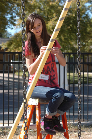 New Vista High student Carley Thompson helps remove tape on a playground swing set at Emerald Elementary School on Wednesday. <br /> October 16, 2011<br /> staff photo/ David R. Jennings