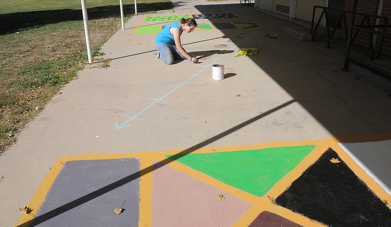 Lea Heinrich, New Vista High, puts final touchups on playground murals for students at Emerald Elementary School on Wednesday. <br /> October 16, 2011<br /> staff photo/ David R. Jennings