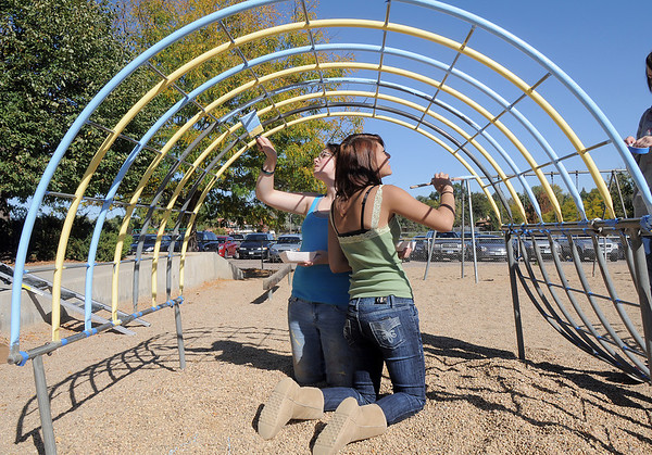 New Vista High students Lea Heinrich, left, and Regina Mata, 16, help paint the playground equipment at Emerald Elementary School on Wednesday. <br /> October 16, 2011<br /> staff photo/ David R. Jennings