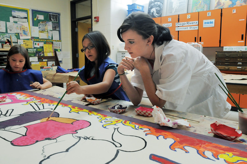 New Vista High student Carley Thompson, 16 right, works with Abrianna Romero, 8, and Rebecca Monahan, 8, as  they paint qa mural for Emerald Elementary School on Wednesday. <br /> October 16, 2011<br /> staff photo/ David R. Jennings