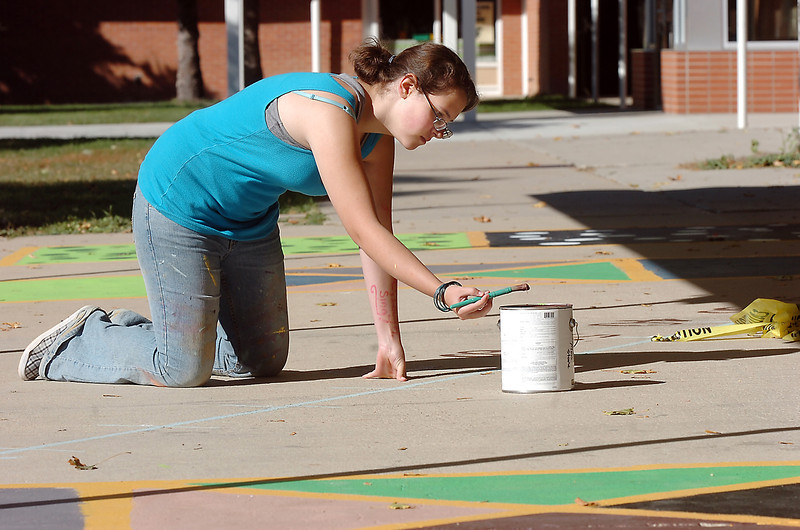 New Vista High student Lea Heinrich, 15, paints numbers on a line  outside of classrooms at Emerald Elementary School on Wednesday. <br /> October 16, 2011<br /> staff photo/ David R. Jennings
