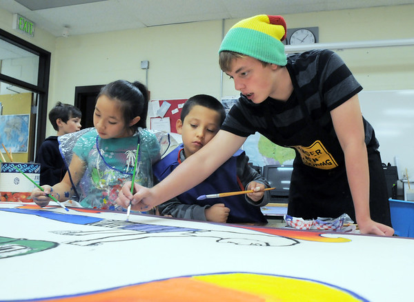 New Vista High student Stephen Mackey, right, demonstrates to Franklin Funets, 8, Hannah Gutierrez, 8, how to paint strips on a figure in a mural for Emerald Elementary School on Wednesday. <br /> October 16, 2011<br /> staff photo/ David R. Jennings