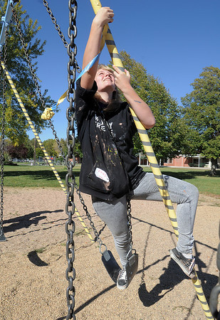 Emily Coffee, New Vista High, climbs a swing set to remove tape from a swing set at Emerald Elementary School on Wednesday. <br /> October 16, 2011<br /> staff photo/ David R. Jennings