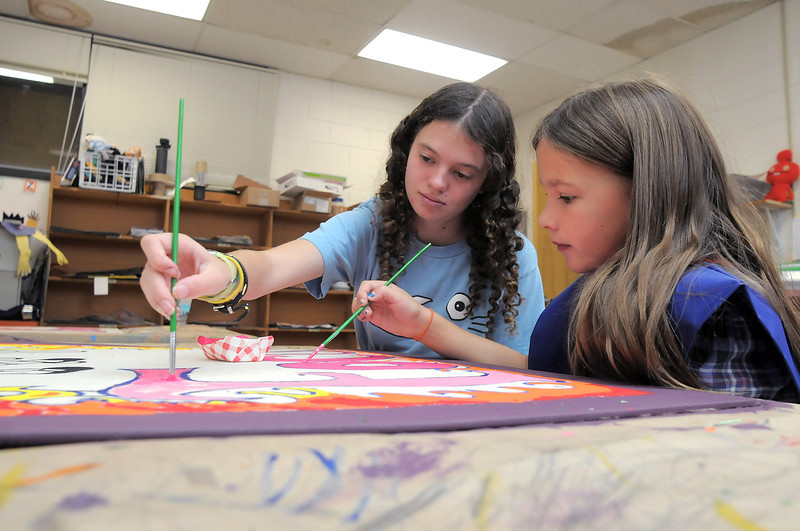 New Vista High student Amber Owen, 17, left, paints one of four murals with Rebecca Monahan, 8, for service week at Emerald Elementary School on Wednesday. <br /> October 16, 2011<br /> staff photo/ David R. Jennings