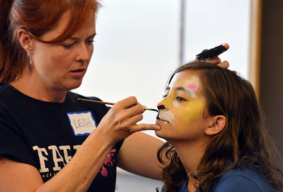 Artist Leah Reddell paints leopard face on Chole Green, 11, as a demonstration to the more than 20 students who attended the Night Visitors Makeup Session by Reddell at the Mamie Doud Eisenhower Public Library on Friday. All of the make up used was professional cosmetic and water based.  June22, 2012 staff photo/ David R. Jennings