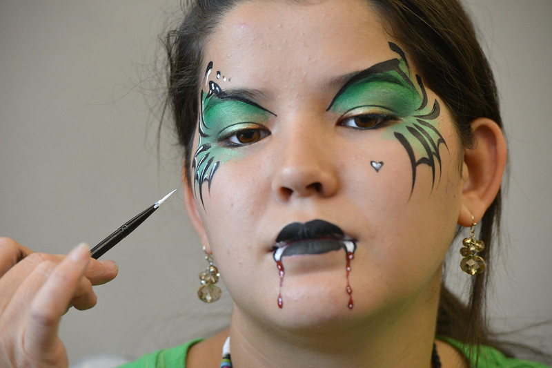 Artist Leah Reddell paints a vampire face on Camille Green, 14, as a demonstration to the more than 20 students who attended the Night Visitors Makeup Session by Reddell at the Mamie Doud Eisenhower Public Library on Friday. All of the make up used was professional cosmetic and water based. <br /> June22, 2012<br /> staff photo/ David R. Jennings