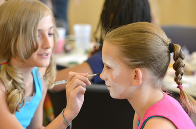Jenna Ammidown, 11, left,  begins to paint a raccoon face on Meredith Frey, 12, during the Night Visitors Makeup Session by taught by Leah Reddell at the Mamie Doud Eisenhower Public Library on Friday.  June22, 2012 staff photo/ David R. Jennings