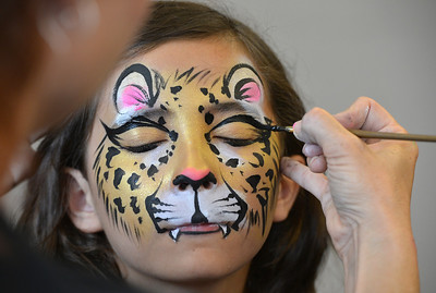 Chole Green, 11, has her face painted as a leopard by artist Leah Reddell during the Night Visitors Makeup Session by Reddell at the Mamie Doud Eisenhower Public Library on Friday. More than 20 students attended the session. June22, 2012 staff photo/ David R. Jennings