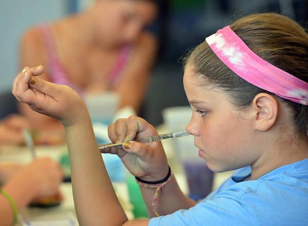 Norah Green, 10, practices using a paint brush on her arm during the Night Visitors Makeup Session by taught by Leah Reddell at the Mamie Doud Eisenhower Public Library on Friday. More than 20 students attended the session.<br /> June22, 2012<br /> staff photo/ David R. Jennings