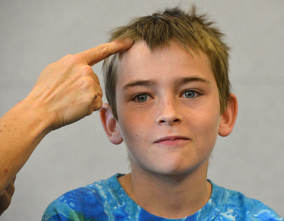 Noah Tibbetts, 10,  before having his face painted as a wolf during the Night Visitors Makeup Session by taught by Leah Reddell at the Mamie Doud Eisenhower Public Library on Friday. More than 20 students attended the session.<br /> June22, 2012<br /> staff photo/ David R. Jennings