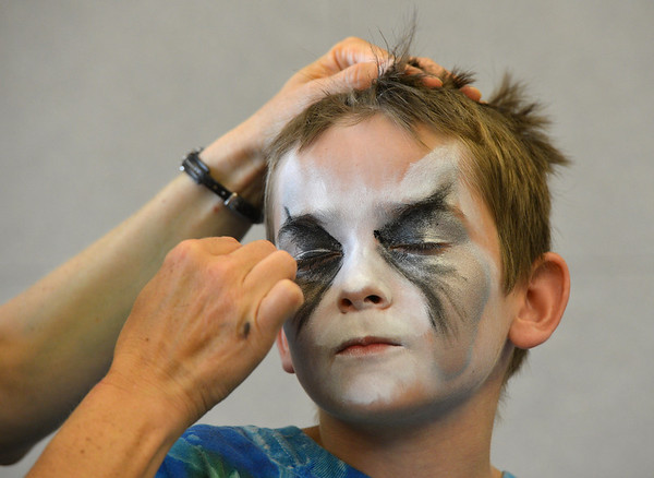Artist Leah Reddell applies black makeup over the white for  Noah Tibbetts, 10,  wolf face  during the Night Visitors Makeup Session by taught by at the Mamie Doud Eisenhower Public Library on Friday. <br /> June22, 2012<br /> staff photo/ David R. Jennings