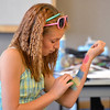 Layla Clark, 14, practices using a sponge to apply makeup on her arm during the Night Visitors Makeup Session by taught by Leah Reddell at the Mamie Doud Eisenhower Public Library on Friday. More than 20 students attended the session.<br /> June22, 2012<br /> staff photo/ David R. Jennings