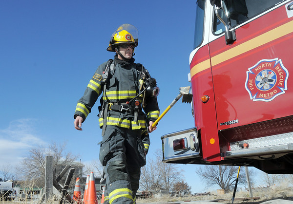"North Metro Fire Rescue engineer Charles Maxwell returns to the fire engines after helping put out a house fire at Weld County Rd. 11 north of Weld County Rd. 4 in Broomfield on Thursday. The resident of the home was not injured. <br /> For more photos please see  <a href=""http://www.broomfieldenterprise.com"">http://www.broomfieldenterprise.com</a><br /> January 23, 2012<br /> staff photo/ David R. Jennings"