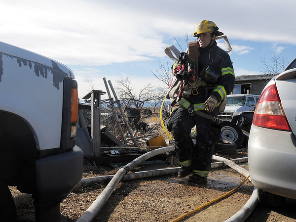 "North Metro Fire Rescue firefighter carries a hose after fighting a fire in a home on Weld County Rd. 11 north of Weld County Rd. 4 in Broomfield on Thursday. The resident of the home was not injured. <br /> For more photos please see  <a href=""http://www.broomfieldenterprise.com"">http://www.broomfieldenterprise.com</a><br /> January 23, 2012<br /> staff photo/ David R. Jennings"