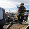 """North Metro Fire Rescue firefighter carries a hose after fighting a fire in a home on Weld County Rd. 11 north of Weld County Rd. 4 in Broomfield on Thursday. The resident of the home was not injured. <br /> For more photos please see  <a href=""""http://www.broomfieldenterprise.com"""">http://www.broomfieldenterprise.com</a><br /> January 23, 2012<br /> staff photo/ David R. Jennings"""