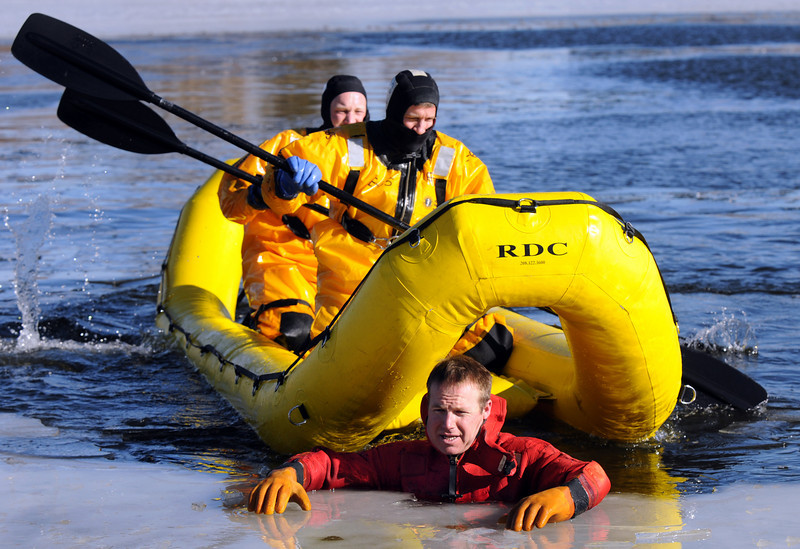 """North Metro Fire Rescue District firefighters Ben Freedman left, and Randy Delaney approach """"victim"""" firefighter Rob Williams in the new water rescue boat during Monday's ice rescue training session at Croke  Reservoir in Northglenn. <br />  <br />  <br /> January 25, 2010<br /> Staff photo/David R. Jennings"""