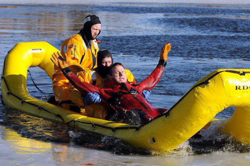 North Metro Fire Rescue District firefighters Rob Williams, right, in red, playing the victim, is pulled into the new water rescue boat by Randy Delaney, center, Ben Freedman and during Monday's ice rescue training session at Croke  Reservoir in Northglenn. <br />  <br />  <br /> January 25, 2010<br /> Staff photo/David R. Jennings