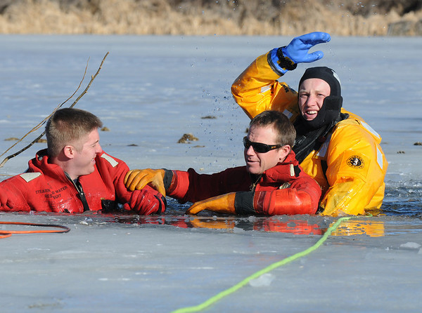 "Firefighter Ben Freedman, right,  North Metro Fire Rescue District, signals to the shore personnel to begin pulling on the rope to rescue  the ""victims"", firefighters Matt Horan, left, and Rob Williams during Monday's ice rescue training session at Croke  Reservoir in Northglenn. <br />  <br />  <br /> January 25, 2010<br /> Staff photo/David R. Jennings"