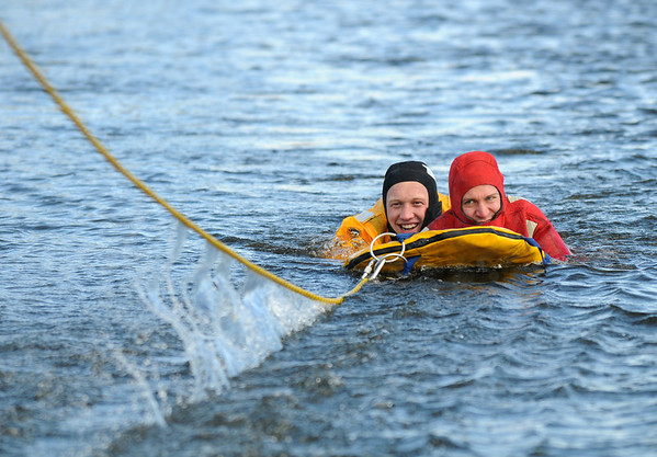 Firefighters Ben Freedman, left, and Rob Williams, rescuer and victim, are pulled out of the icy water during Monday's North Metro Fire Rescue District ice rescue training session at Croke  Reservoir in Northglenn. <br />  <br />  <br /> January 25, 2010<br /> Staff photo/David R. Jennings