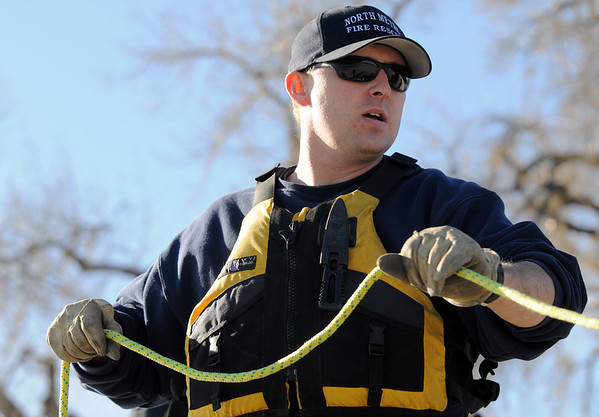 Engineer Jason Crownover, North Metro Fire Rescue District, pulls on the rope to bring a victim to the shore during Monday's ice rescue training session at Croke  Reservoir in Northglenn. <br />  <br />  <br /> January 25, 2010<br /> Staff photo/David R. Jennings