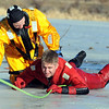 "North Metro Fire Rescue District firefighter Ben Freedman, left, helps guide  ""victim"" Matt Horan along the ice during Monday's ice rescue training session at Croke Reservoir in Northglenn. <br />  <br />  <br /> January 25, 2010<br /> Staff photo/David R. Jennings"