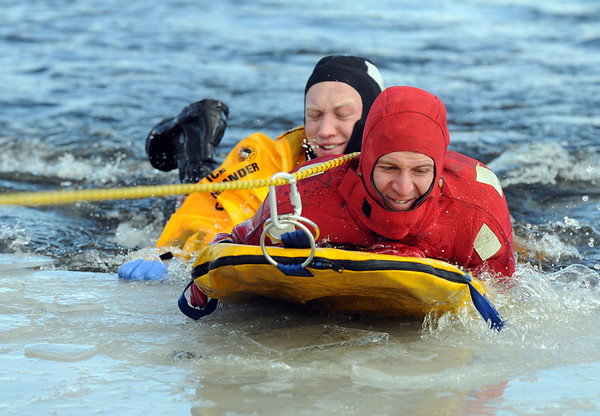 North Metro Fire Rescue District firefighters Ben Freedman, left, and Rob Williams are pulled out of the ice as rescuer and victim during Monday's ice rescue training session at Croke  Reservoir in Northglenn. <br />  <br />  <br /> January 25, 2010<br /> Staff photo/David R. Jennings