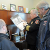 Fire Chief Joe Bruce shows his family firefighting photo album to Fairmont Fire chief Don Angell, right, and  Fairmont Fire  board member Tom Young during the public open house of the new North Metro Fire Rescue District administration building on Thursday.  Chief Bruce worked with Chief Angell and Young on the Golden Fire Department.<br /> <br /> January 20, 2011<br /> staff photo/David R. Jennings