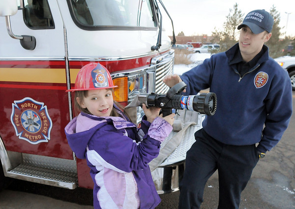 Kayliana Schild, 6, left, holds a fire nozzle with firefighter/paramedic Rob Perry during the public open house of the new North Metro Fire Rescue District administration building on Thursday.<br /> <br /> January 20, 2011<br /> staff photo/David R. Jennings